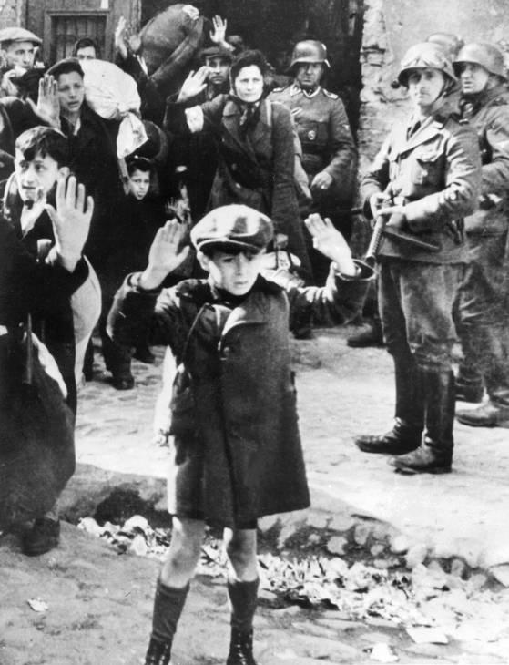 Varşova yahudi gettosunda silahlı Alman askerleri tarafından kuşatılmış elleri havada küçük bir çocuk ve yetişkinler.